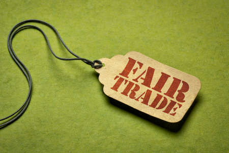 fair trade sign a paper price tag against green background - conscious shopping concept