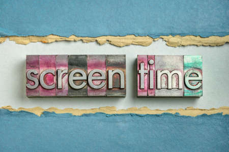 screen time word abstract in gritty vintage letterpress metal types against colorful handmade rag paper, digital media use and mental health concept