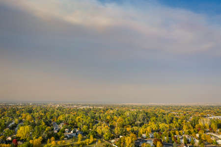 fall colors under wildfire smoke - aerial cityscape of Fort Collins in northern Colorado with smoke from Cameron Peak (CO) and Mullen (WY) Fires (October 2020), poor air quality with high PM2.5 index