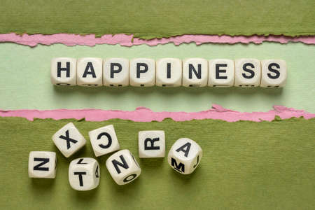 happiness word abstract in wooden letter cubes against paper abstract in green tones, personal development concept