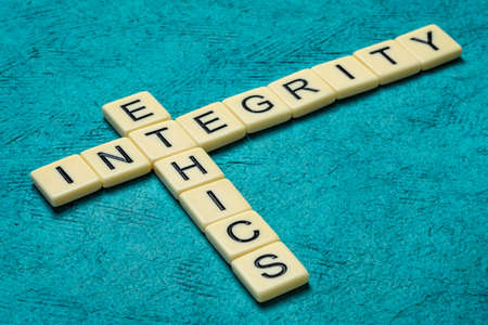 integrity and ethics crossword in ivory letters against textured handmade bark paper, moral obligations and conduct concept