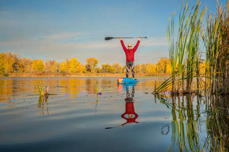 happy senior male stand up paddler on a calm lake, fall scenery in northern Colorado