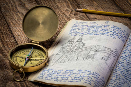 Vintage travel journal with handwriting and pencil sketches (property release attached) and old brass compass.