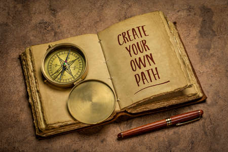 create your own path - handwriting in an antique leather-bound journal with a stylish pen and vintage brass compass, lifestyle, career and personal development concept