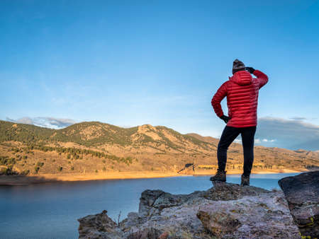 male hiker in a down jacket on a cliff overlooking Horsetooth Reservoir, popular recreation destination for boating, hiking and biking in northern Colorado, fall scenery at sunrise