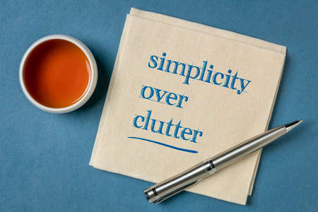 simplicity over clutter inspirational concept - writing on a napkin with a cup of tea, decluttering and minimalism Stock Photo