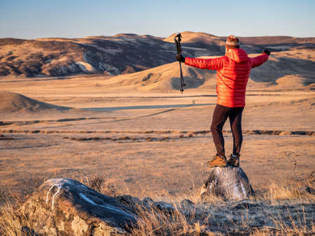 happy male hiker with trekking post at foothills of Rocky Mountains in northern Colorado - fall scenery at sunrise in Soapstone Prairie Natural Area near Fort Collins Foto de archivo