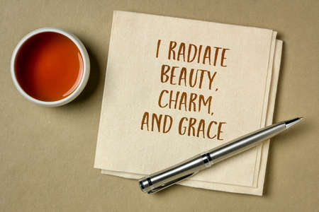 I radiate beauty, charm and grace - positive affirmation, handwriting on a napkin with a cup of tea, positivity and personal development concept