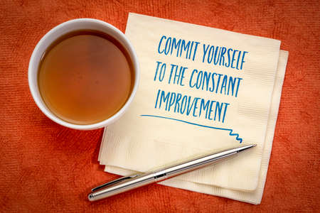 commit yourself to constant improvement - handwriting on a napkin with a cup of tea, goal setting, resolutions, self improvement and personal development concept 写真素材