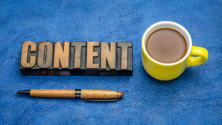 content - word abstract in vintage letterpress wood type printing blocks against handmade bark paper with a cup of coffee, media and communication concept