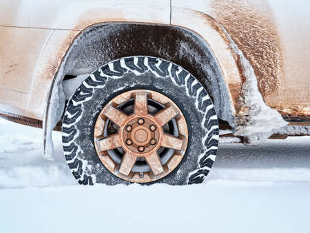Closeup of all-terrain tire and wheel of dirty 4x4 SUV car or truck  - winter travel and recreation concept Foto de archivo