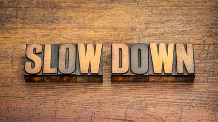 slow down word abstract in vintage letterpress wood type against rustic wooden background, work, stress and lifestyle concept Standard-Bild