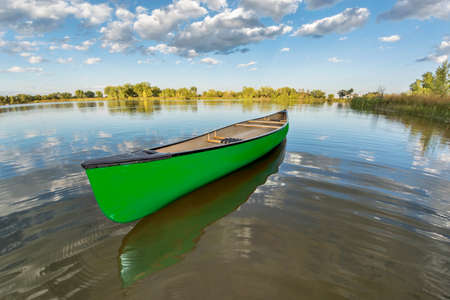 green canoe on a calm lake in a fisheye perspective, late summer in Arapaho Bend Natural Area, Fort Collins, Colorado