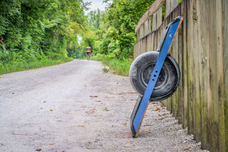 gravel bike trail with one-wheeled electric skateboard and a distant cyclist, summer scenery in Missouri