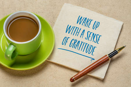 wake up with a sense of gratitude inspirational handwriting on a napkin with a cup of coffee, positivity and personal development concept