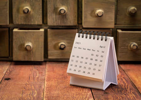 April 2021 - spiral desktop calendar on a weathered barn wood table with rustic apothecary drawers in background, time and business concept