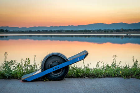 One-wheeled electric skateboard (personal transporter) on a lake shore against sunset sky over Rocky Mountains.