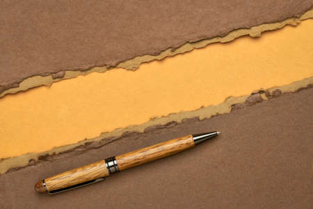 paper abstract in brown and orange with a copy space and a stylish pen - sheets of handmade paper,  diagonal blank web banner
