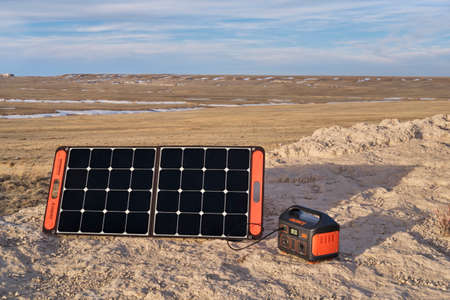 Nunn, CO, USA - March 28, 2021: Jackery Explorer 500, 518Wh lithium Portable Power Station, is beeing charged by a solar panel in a remote location in Pawnee National Grassland, early spring scenery. 新聞圖片