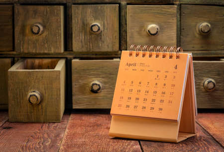 April 2021 - spiral desktop calendar with English and Chinese symbols on a weathered barn wood table with rustic apothecary drawers in background, time and business concept 版權商用圖片