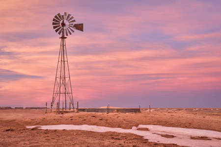 windmill with a pump and cattle water tank in shortgrass prairie, Pawnee National Grassland in northern Colorado, winter or early spring scenery