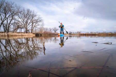 senior male stand up paddler is starting his paddling season on a  lake in Colorado