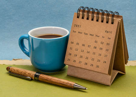 April 2021 - spiral desktop calendar with a cup of coffee against paper landscape abstract, time and business concept