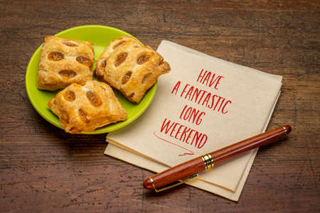 have a fantastic long weekend - inspirational handwriting on a napkin with strudel bites 版權商用圖片