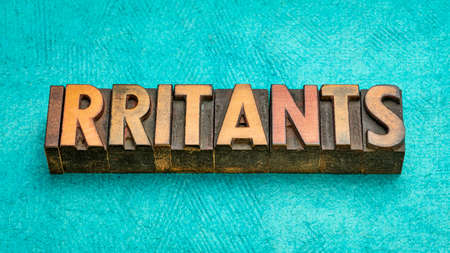 irritants word abstract in vintage letterpress wood type, a substance that causes an allergic reaction. 版權商用圖片