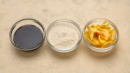 Dried slices of yacon tuber, syrup and powder in small glass bowls against textured paper. Yacon contains inulin, a complex sugar, which promotes healthy probiotics. Superfood concept.