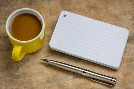 a stack of blank index cards with a cup of coffee and  a pen against textured bark paper