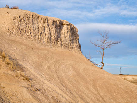 Early spring or winter over badlands with a lonely tree and windmill in Pawnee National Grassland in northern Colorado (Main Draw OHV Area) 版權商用圖片