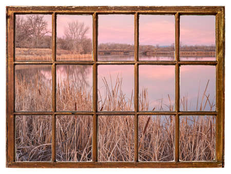 early spring dawn over a calm lake with reeds as seen from a vintage cabin window 版權商用圖片