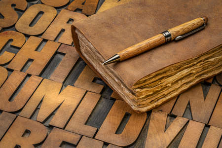 retro leatherbound journal or book with decked edge handmade paper pages and a stylish pen on a letterpress wood type alphabet, journaling concept
