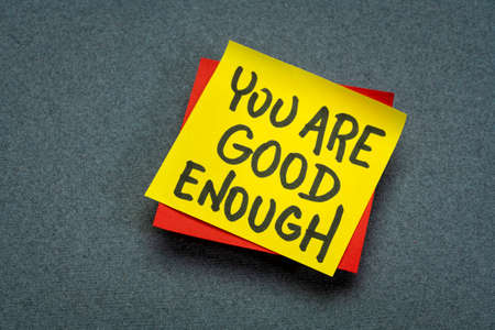 you are good enough inspirational concept - handwriting in black ink on a sticky note, positive affirmation, self confidence and personal development 版權商用圖片