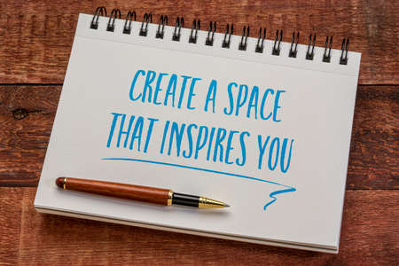create a space that inspires you - inspirational writing in a spiral notebook with a stylish pen against weathered barn wood table, business and working from home concept 版權商用圖片