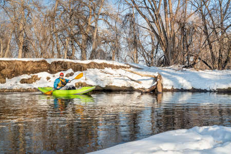 senior male paddler is paddling an inflatable whitewater kayak on a small river - Poudre River in Fort Collins, Colorado, winter or early spring scenery 版權商用圖片