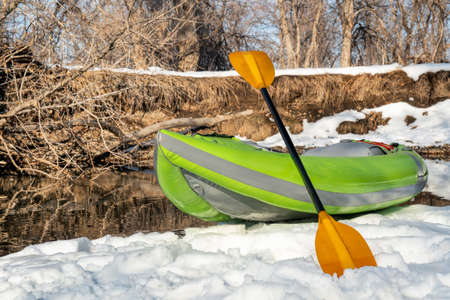 inflatable whitewater kayak on a small river shore - Poudre River in Fort Collins, Colorado, winter or early spring scenery