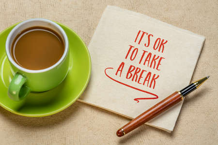 It is OK to take a break - inspirational handwriting on a napkin with a cup of coffee, self care, stress, overworking concept