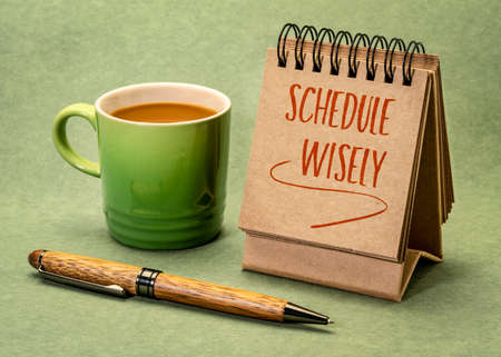 schedule wisely - reminder in desktop calendar with a cup of coffee, business and personal planning concept 版權商用圖片