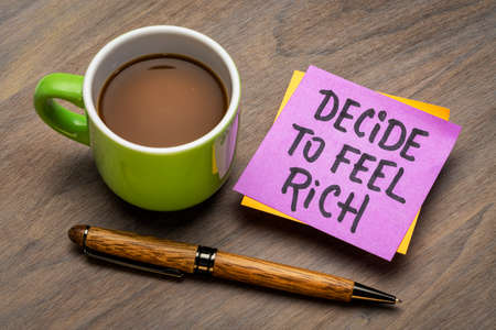 decide to feel rich - inspirational advice on a sticky note with a cup of coffee, positive mindset and personal development concepot