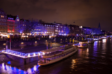 The Weser in the evening with many colorful lights reflected in the water, ships are at the harbor
