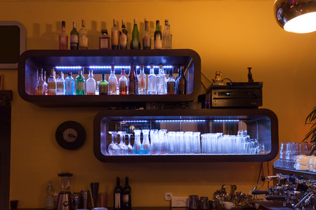 Shelf with glasses and bottles in a pub under atmospheric light Stok Fotoğraf