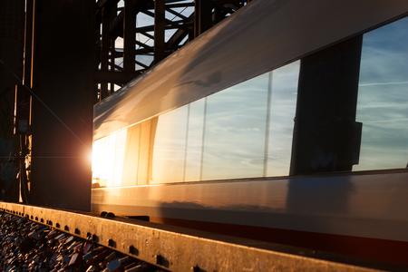 Train goes in the evening sun over an iron bridge