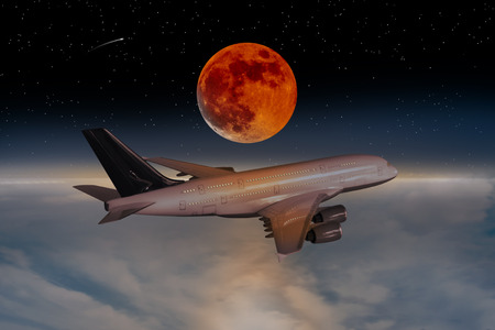 Airliner flies above the clouds during a lunar eclipse