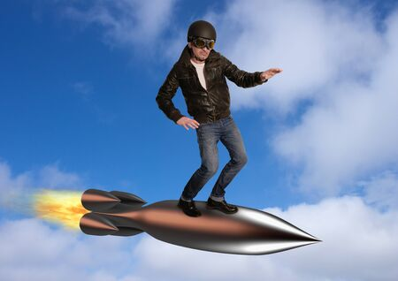 Superhero flies in the clouds, standing on a rocket Stock Photo