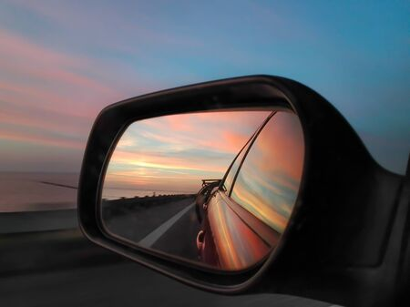 The side mirror of a car reflects the evening sky Stock fotó