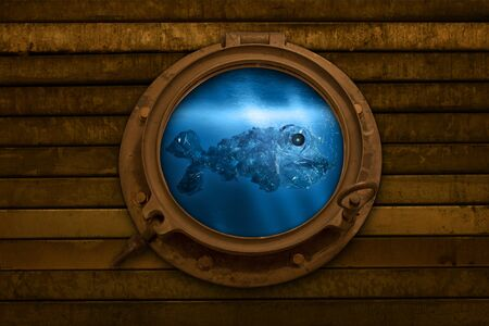 Looking through a porthole into the underwater world, a plastic fish comes by Фото со стока