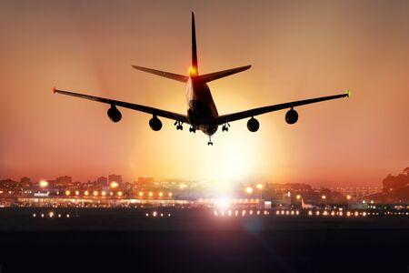 Passagierflugzeug landet in der Dämmerung, im Hintergrund sind die Lichter des Flughafens zu sehen