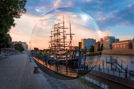Looking through a glass globe, sailing ships lie on the banks of the river Weser in the Hanseatic city of Bremen at dawn